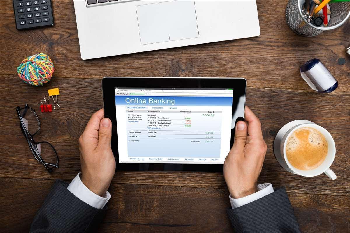 mani di businessman reggono un tablet con schermata su un tavolo con la colazione