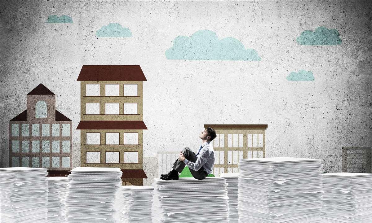 uomo d'affari seduto su una pila di documenti su uno sfondo di palazzi