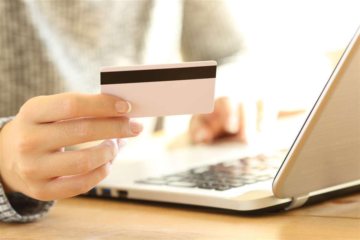 persona seduta al pc con carta di credito in mano