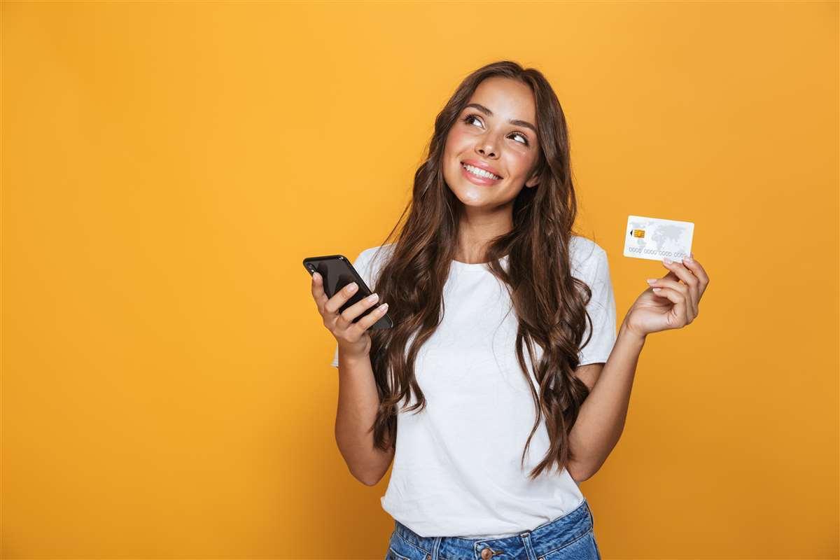 ragazza sorridente tiene una carta di credito in una mano e lo smartphone nell'altra