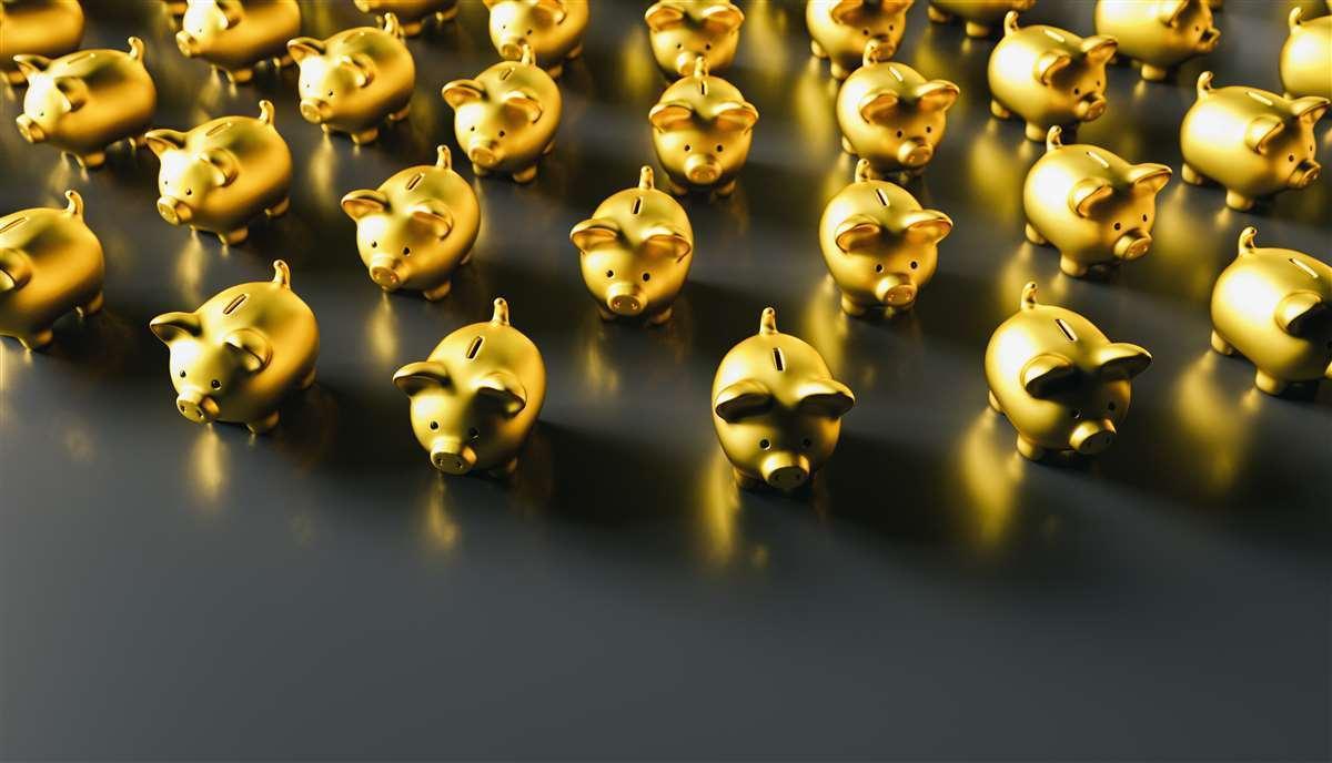 tanti piccoli salvadanai d'oro schierati su una superficie nera
