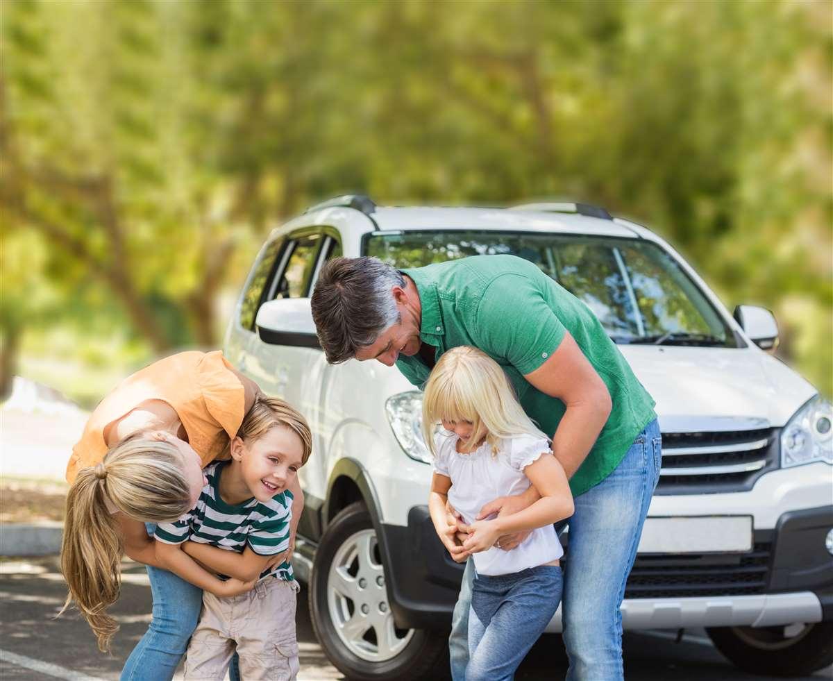 famiglia con bambini piccoli davanti a macchina