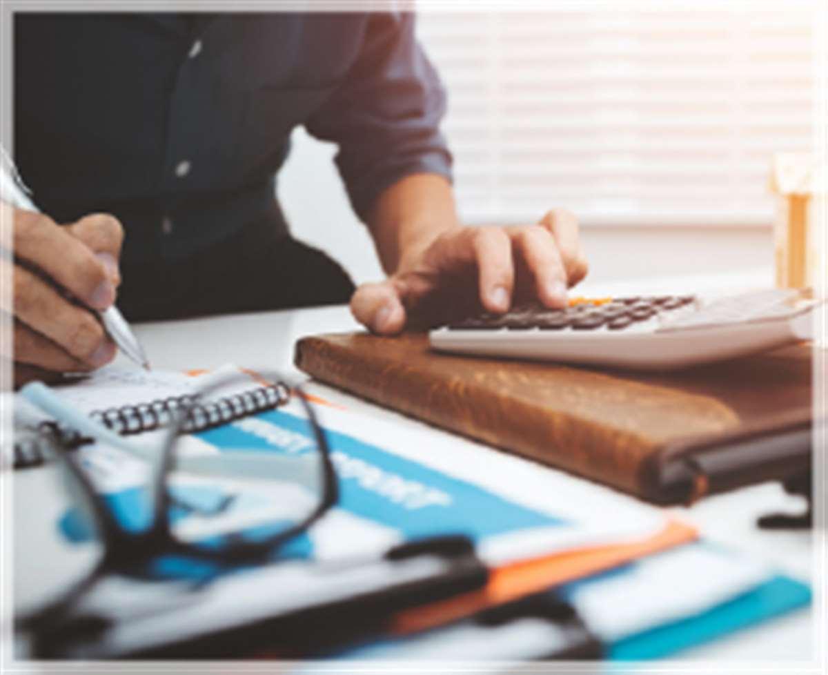 Mani di uomo che schiacciano i tasti di una calcolatrice e scrivono su un tavolo da ufficio