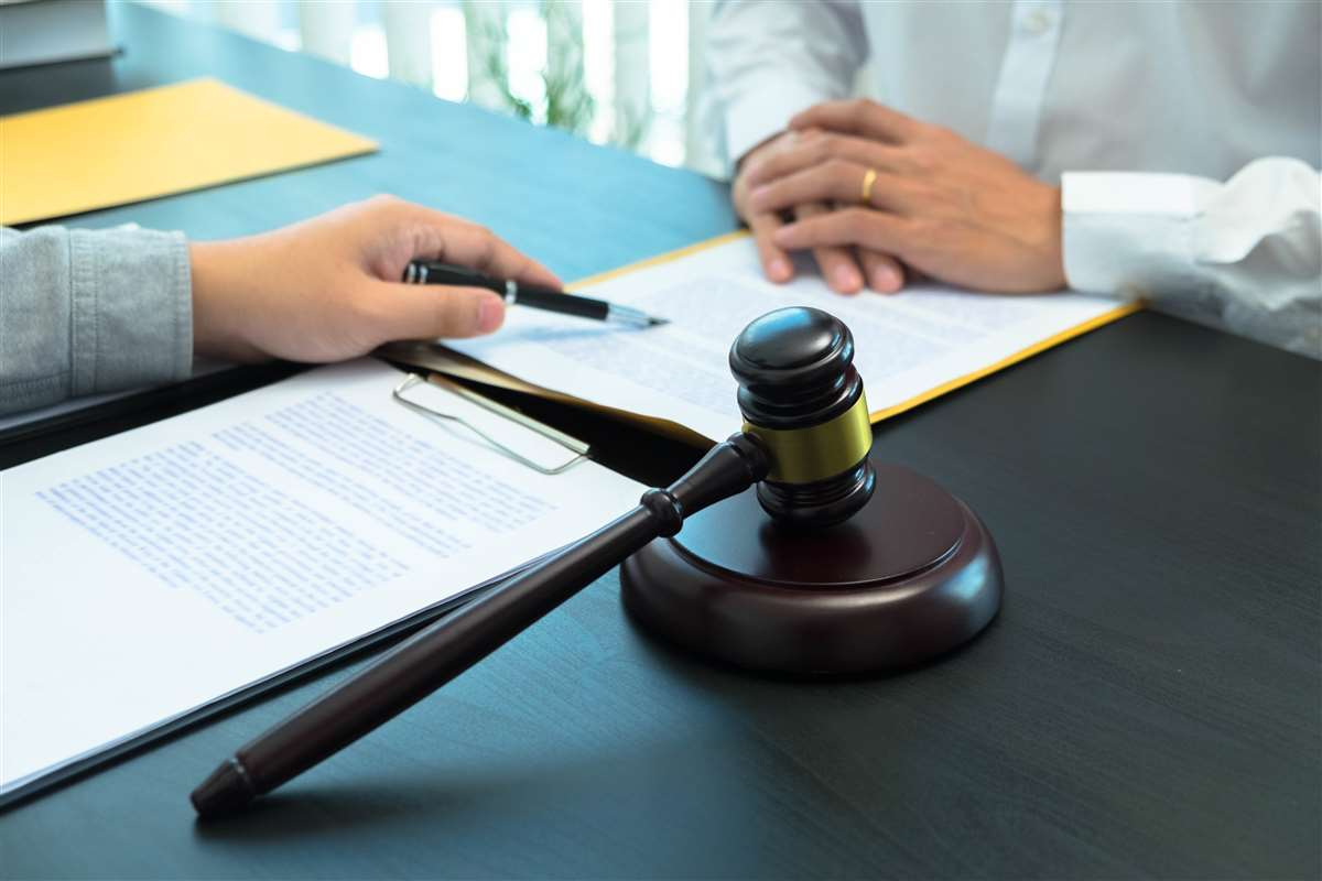 mani su una scrivania vicino a un martelletto che indicano una riga di un documento