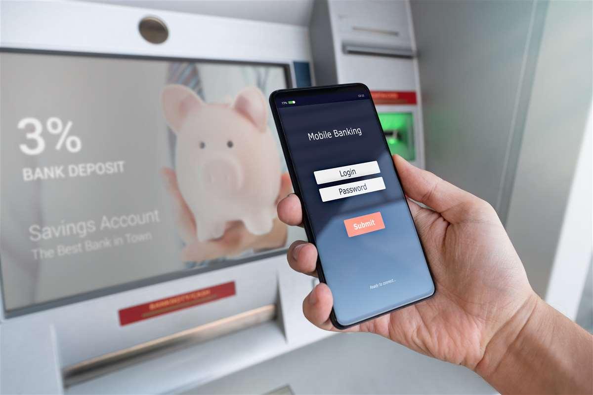 mano di uomo che regge uno smartphone davanti a uno sportello atm di una banca